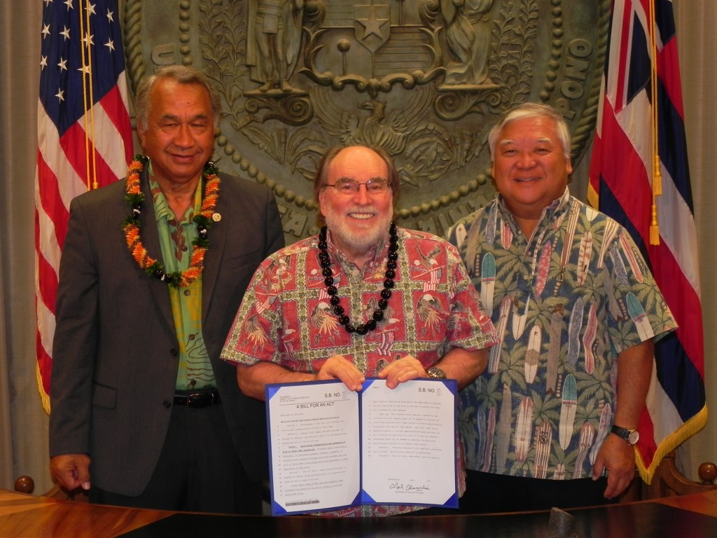Senator Gil Kahele, Governor Neil Abercrombie, and Senator Clarence Nishihara at the signing of a bill to prohibit the possession, transport, or release of deer in Hawaii.