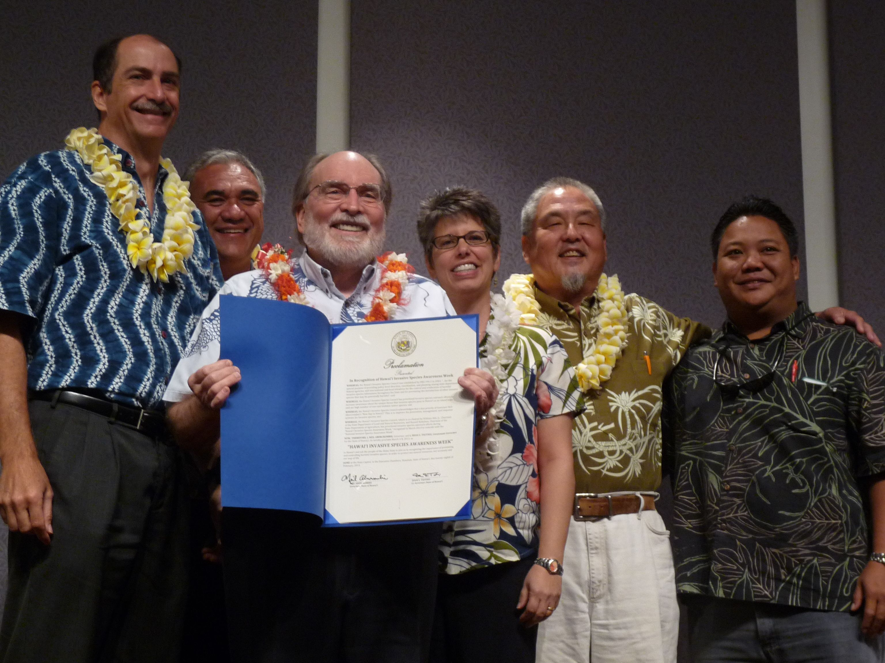 HISC members receive Governor's proclamation for Hawaii Invasive Species Awareness Week in March. From left: DOH Deputy Director Gary Gill, DLNR Chairperson William J. Aila, Gov. Neil Abercrombie, UH CTAHR Dean Maria Gallo, HDOA Chairperson Russell Kokubun, DOT David Rodriguez.