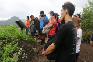 Group of visitors reading educational signage at Kawainui-Hāmākua marsh